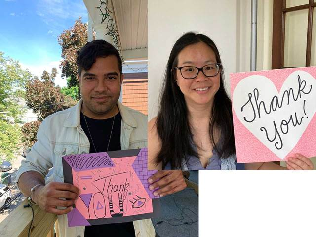 two person holding pink thank-you signs