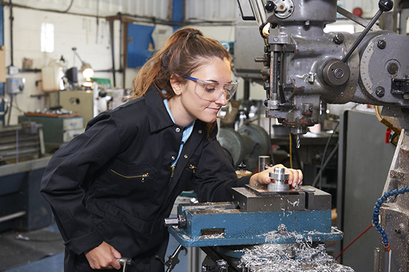 Female Apprentice Engineer Working On Drill In Factory