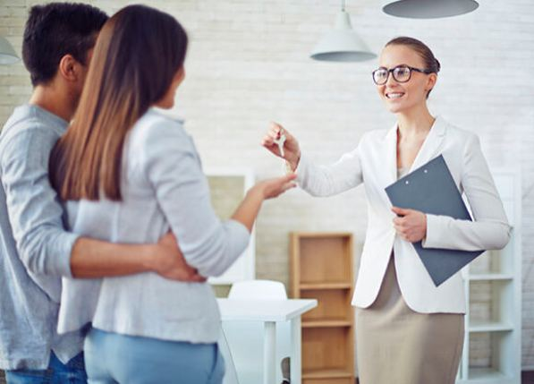Female broker giving young couple key from new flat