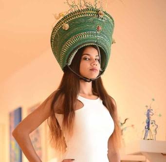Julissa Ragunauth wears a hat created by artist Daniel Lanzilotta. Behind her are some of Lanzilotta's sculptures.