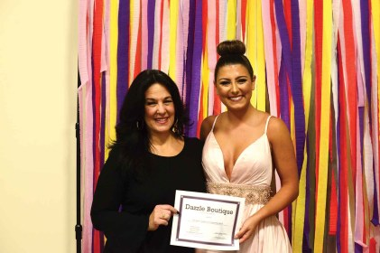 Laurye Natale of Dazzle Boutique presents a certificate to Alyssa Anderson, the first ever Dazzle Girl of the store.