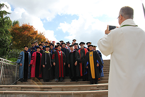 Admission counselor Rev. John Dreyer takes a photo of the faculty at the 2018 graduation service.