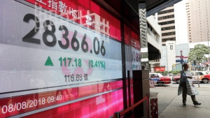 A man walks past a bank's electronic board showing the Hong Kong share index in Hong Kong Wednesday, Aug. 8, 2018. (AP Photo/Vincent Yu)