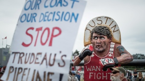 A man listens near an effigy of Prime Minister Justin Trudeau as protesters opposed to the Trans Mountain pipeline expansion rally ahead of a decision by Liberal cabinet on the project, in Vancouver, on Sunday June 9, 2019. THE CANADIAN PRESS/Darryl Dyck