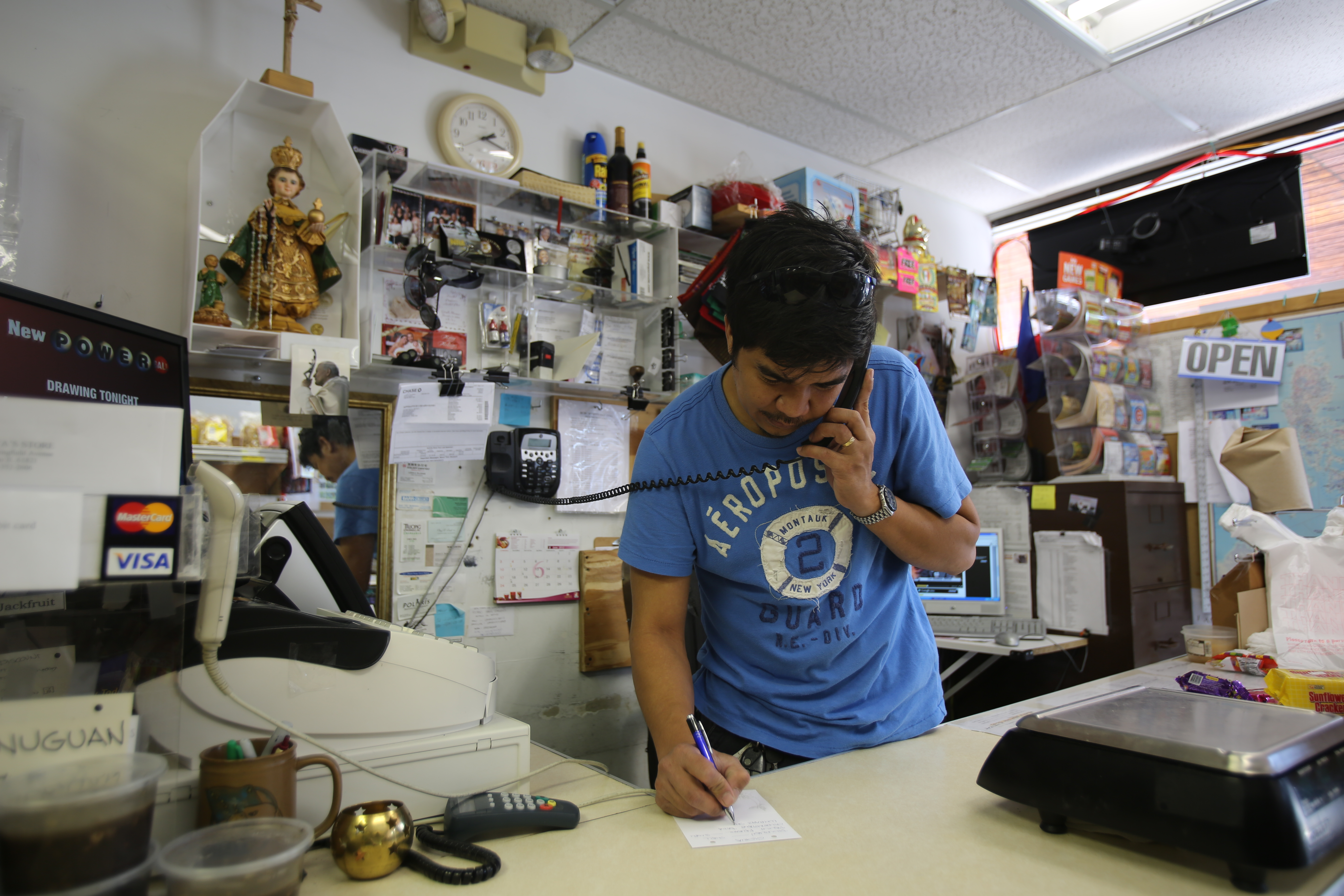 Eric Maligaya takes a call at Maligayas, a grocery store that caters explicitly to Filipino customers. He is the son of the owner and estimates that 70 to 80 percent of the customers are Filipinos looking for meats like adodo and menudo, steamed buns or siapao, sweet fruits or coconut milk.