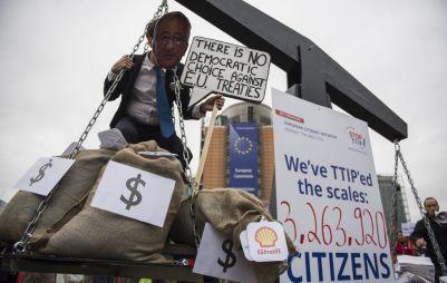 """Un activista disfrazado de Juncker porta una pancarta """"No hay opción democrática alguna contra los tratados de la UE."""""""