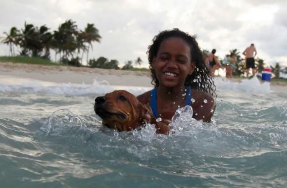 Una niña juega con su perro en la playa, el 4 de octubre de 2009. (REUTERS/Desmond Boylan)