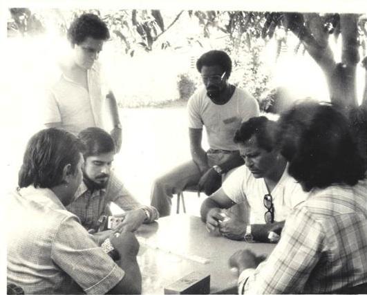 Carlos Muñiz Varela es el de la barba, que juega dominó. Detrás, de pie, Reinaldo Pérez, el padre de Residente.