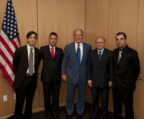 Ernesto Hernández Busto a la derecha de Bush, con la nalga pegada a  la bandera de los Estados Unidos. El ex Presidente, como podrán  apreciar, lleva su cara más inteligente. Foto: Bush Instituto.