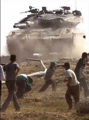 Niños palestinos tiran piedras a un tanque israelí.