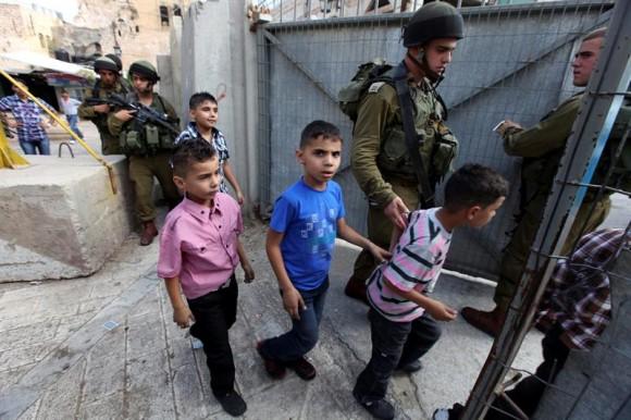 Soldados israelíes vigilan hoy en Hebrón a diversos niños palestinos que fueron arrestados en el primer día del Eid al-Fitr en Hebron, Cisjordania,por jugar con sus armas de juguete en Hebron – EFE/ABED AL HASHLAMOUN