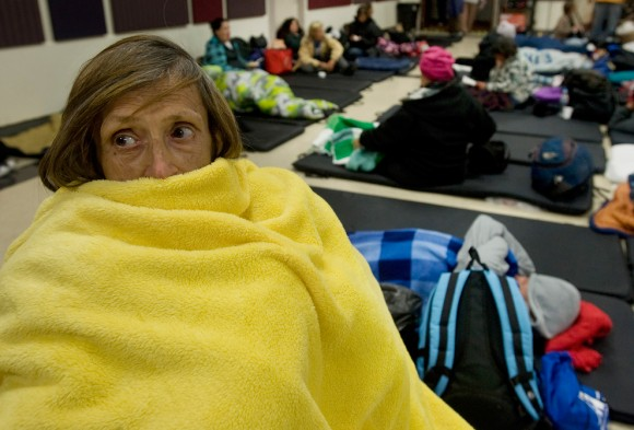 Beverly McKinney, de 63 años, duerme en su silla de ruedas en California. Una lesión de rodilla le impide dormir en el suelo, dijo. Sus posesiones son dos mantas, unos pocos alimentos, ropa de repuesto y las cenizas de su marido. (Foto: Schauer Mindy / Associated Press / Orange County)