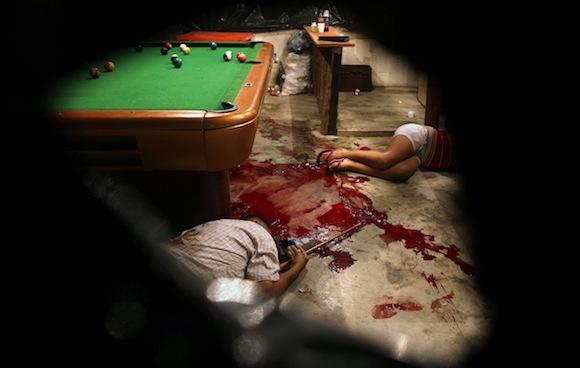 En este 11 de marzo 2012 la foto, los cuerpos de Lesbia Altamirano y Orberá Wilmer tumbarse en el suelo de un pasillo de la piscina después de ser atacado por desconocidos enmascarados en Choloma, en las afueras de San Pedro Sula, Honduras. Una ola de violencia que ha hecho de Honduras uno de los lugares más peligrosos del mundo, con una tasa de homicidios de aproximadamente 20 veces la de la tasa de EE.UU., según un informe de 2011 de las Naciones Unidas. (AP Photo / Esteban Felix)