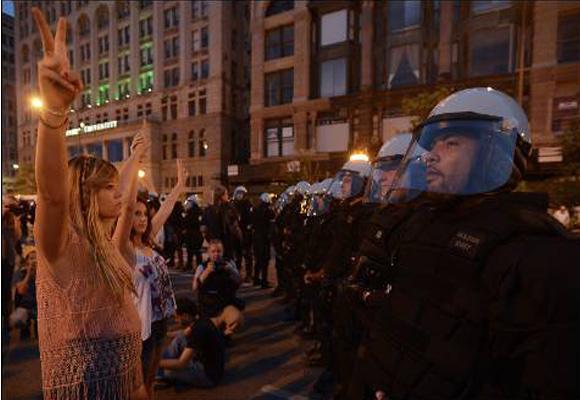 Manifestantes hacen con sus dedos la señal de la victoria mientras protestan contra la cumbre de la OTAN en una calle de Chicago (EEUU). EFE/TANNEN MAURY