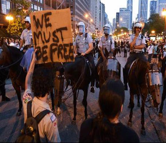 """Un manifestante sostiene un cartel que dice """"Debemos ser libres"""" mientras protesta contra la cumbre de la OTAN en una calle de Chicago (EEUU). EFE/TANNEN MAURY"""