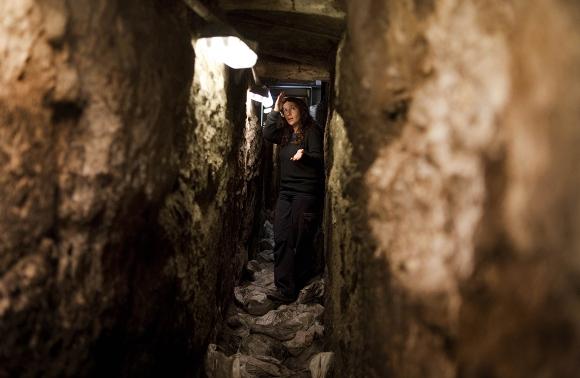La arqueóloga Annete Nagar muestra el túnel de drenaje del Segundo Templo, de 2000 años de antigüedad, en la Ciudad Vieja de Jerusalén en el lado oeste del Muro de los Lamentos judío, el 25 de enero de 2011. Arqueólogos israelíes han terminado el trabajo, que comenzó en 2004, en el túnel que se inicia en un sitio cerca de la mezquita Al-Aqsa, punto de inflamación dentro de los muros de la Ciudad Vieja de Jerusalén, dijeron las autoridades. (Menahem Kahana / AFP / Getty Images)