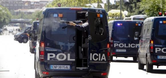 Un agente dispara pelotas de goma contra los manifestantes desde una furgoneta policial.