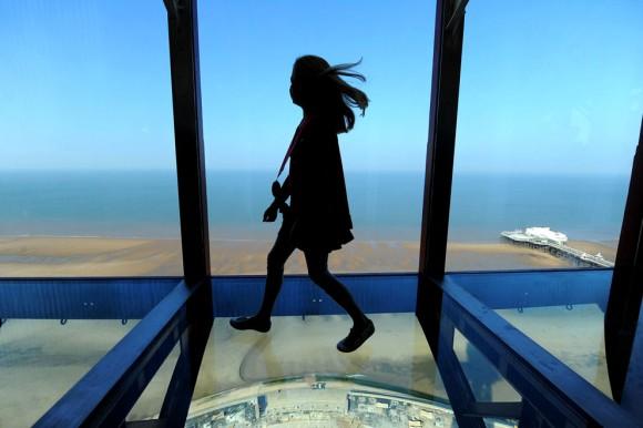 Amber Houghton, ganadora de un concurso, es una de las primeras personas en caminar sobre la nueva pasarela de vidrio en la cima de la torre de Blackpool en Blackpool, Inglaterra, el 1 de septiembre de 2011. Foto: Andrew Yates/AFP/Getty Images.