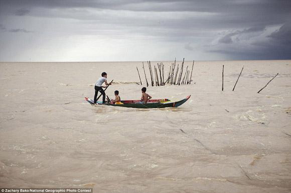 Unos niños luchan contra la tormenta en Cambodia. Foto: Zachary Bako.