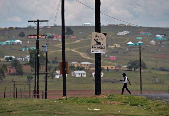 Un niño camina junto a un cartel con la imagen de Nelson Mandela en Qunu (Sudáfrica), cerca de la granja donde el líder sudafricano paso su infancia. Foto: CARL DE SOUZA (AFP)