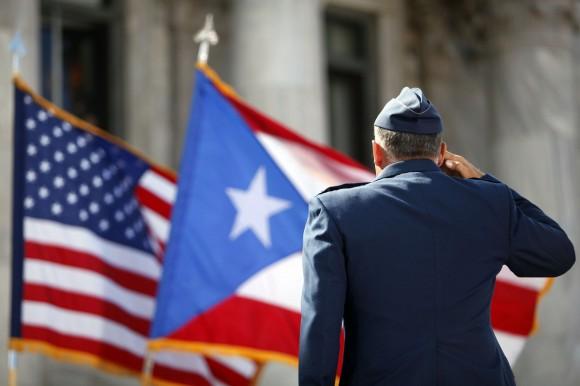 Un miembro de la Guardia de Honor del Ejército de EE.UU. rinde homenaje a las banderas de Puerto Rico y Estados Unidos.