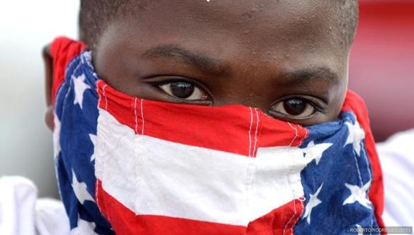 Un joven se tapa la cara con una bandera estadounidense durante la marcha de este lunes.