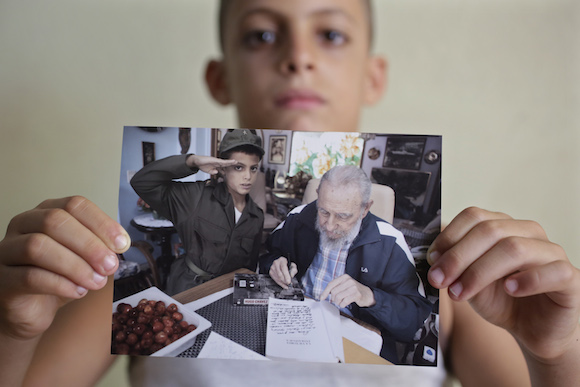 "Eight-year-old Marlon Mendez, who claims to be an admirer of Cuba's former president Fidel Castro, shows a book "" La Victoria Estrategica"" of Fidel Castro dedicated by Castro for him , in San Antonio de los Banos, outside Havana City, August 23, 2014. Cuba's former president Fidel Castro invited him little after he learned about Marlon Mendez who is a bigger admirer from him. REUTERS/Enrique De La Osa (CUBA  - Tags: POLITICS SOCIETY)"