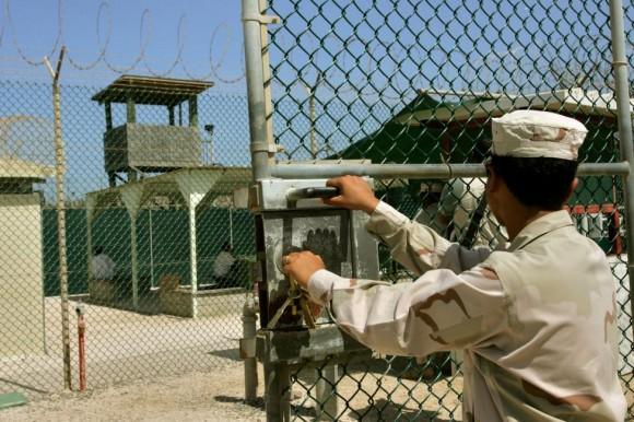 Un guardia se abre una puerta, mientras que en el fondo dos detenidos se sientan en un área de descanso detrás de esgrima, en el recinto del Campo Delta 4 prisión administrada militar, en la Base Naval de la Bahía de Guantánamo Estados Unidos, Cuba 27 de junio 2006. Foto: Brennan Linsley/ Reuters.