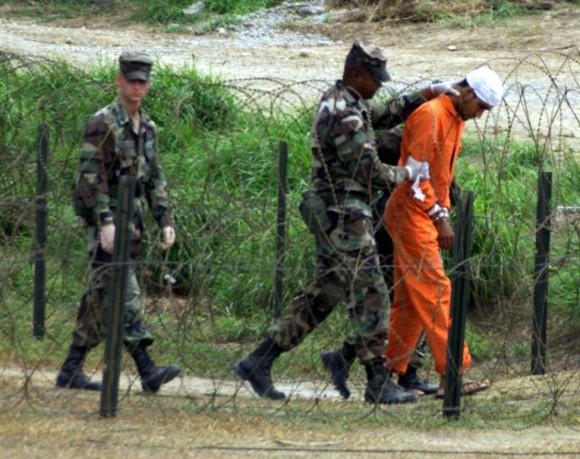 Policía Militar en el campamento de rayos X en la Base Naval de Guantánamo, en Cuba, llevar a un detenido a una sala de interrogatorios, 06 de febrero 2002. Foto: Marc Serota/ Reuters.