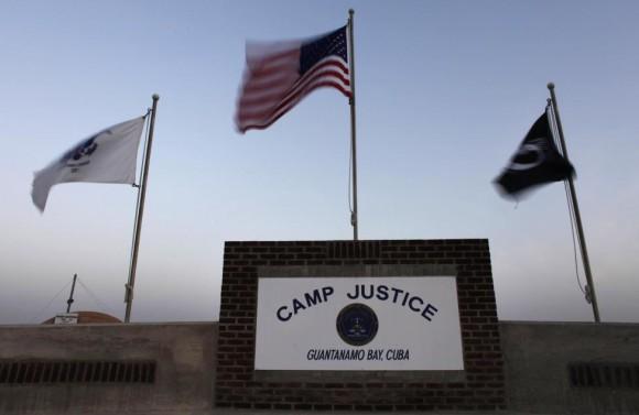 Banderas ondean por encima del letrero a la entrada de Campamento Justicia. Foto: Brennan Linsley/ Reuters.