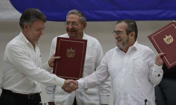 El Presidente Juan Manuel Santos y Timoleón Jiménez, líder de las FARC-EP se dan la mano. Raúl, al centro. Foto: Ramón Espinosa/ AP