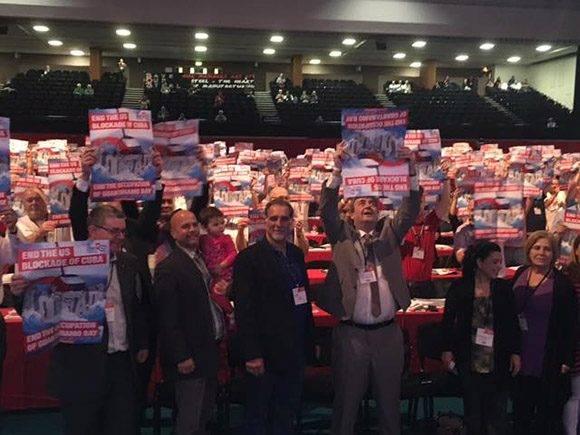 Gerardo y René levantan sus pancartas en el acto de la Unión de Delegados en el Reino Unido. Foto: Cuba Solidarity Campaing/ Facebook.