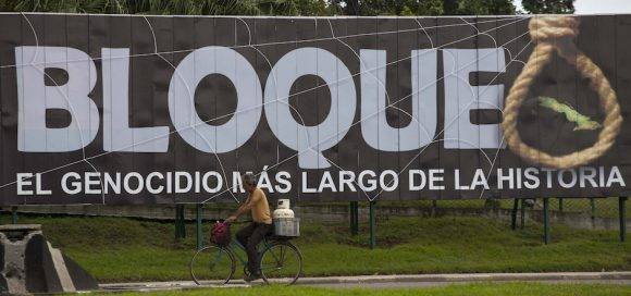 "A man carries a gas cylinder on the back of his bicycle as he passes a billboard that reads in Spanish ""Blockade: The longest genocide in History"" in Havana, Cuba, Tuesday, Jan. 26, 2016. The Obama administration is loosening the U.S. trade embargo on Cuba with a new round of regulations allowing American companies to sell to Cuba on credit and export a limited number of products to the Cuban government, officials said Tuesday. (AP Photo/Desmond Boylan)"