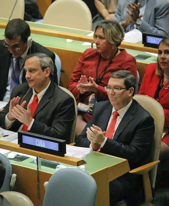 Cuba's Foreign Minister Bruno Rodríguez, right, applaud with his delegation during a meeting of the U.N. General Assembly, Wednesday Oct. 26, 2016 at U.N. headquarters. The United States has abstained for the first time in 25 years on a U.N. resolution condemning America's economic embargo against Cuba, a measure it had always vehemently opposed. (AP Photo/Bebeto Matthews)