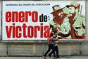 Dos cubanos pasan junto a un cartel que celebra el triunfo de la Revolución Cubana