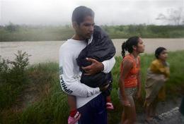 Residentes que esperaban por el transporte, bajo la lluvia del huracán Ike, en Herradura, Pinar del Rio. (AP)
