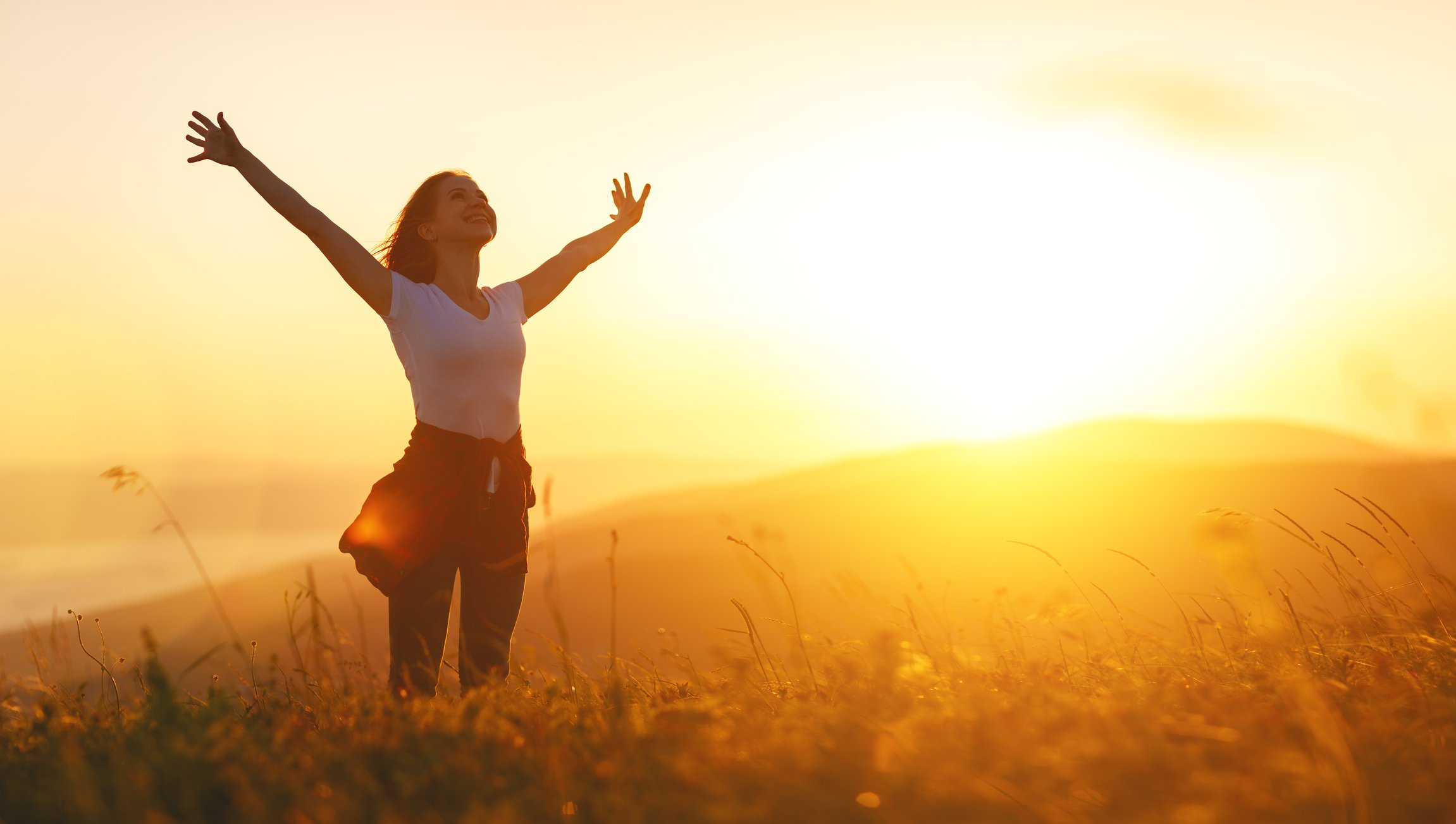 Happy woman   on sunset in nature iwith open hands