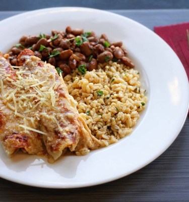 Savory chicken enchiladas are topped with sour cream gravy and red enchilada sauce, and served with cilantro-lime brown rice and chili beans.