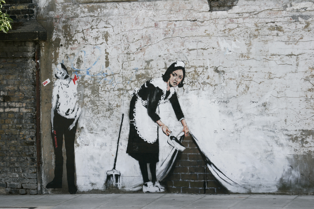 A mural of a maid sweeping, created by graffiti artist Banksy.