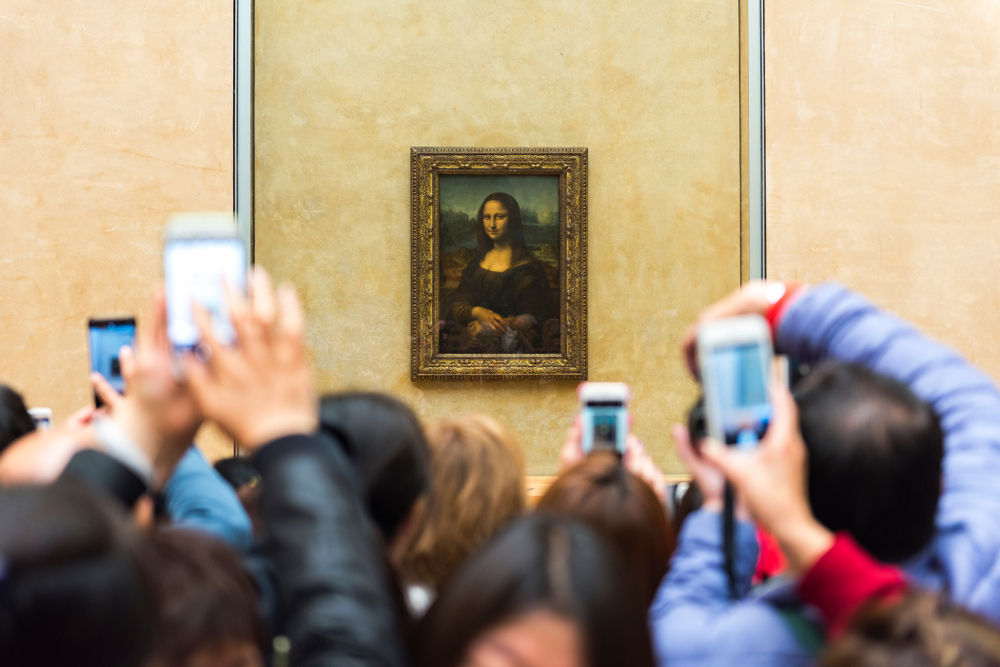 Scores of people gather in front of the Mona Lisa, one of the most revered portraits in the history of art, at the Louvre museum in Paris.
