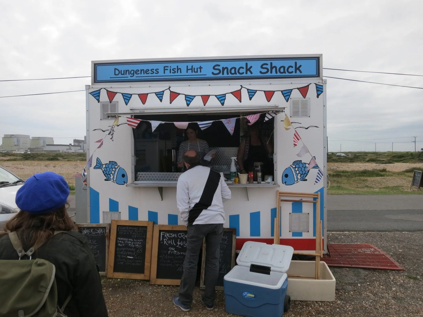 Man standing at red white and blue bunting strewn Dungeness Snack Shack