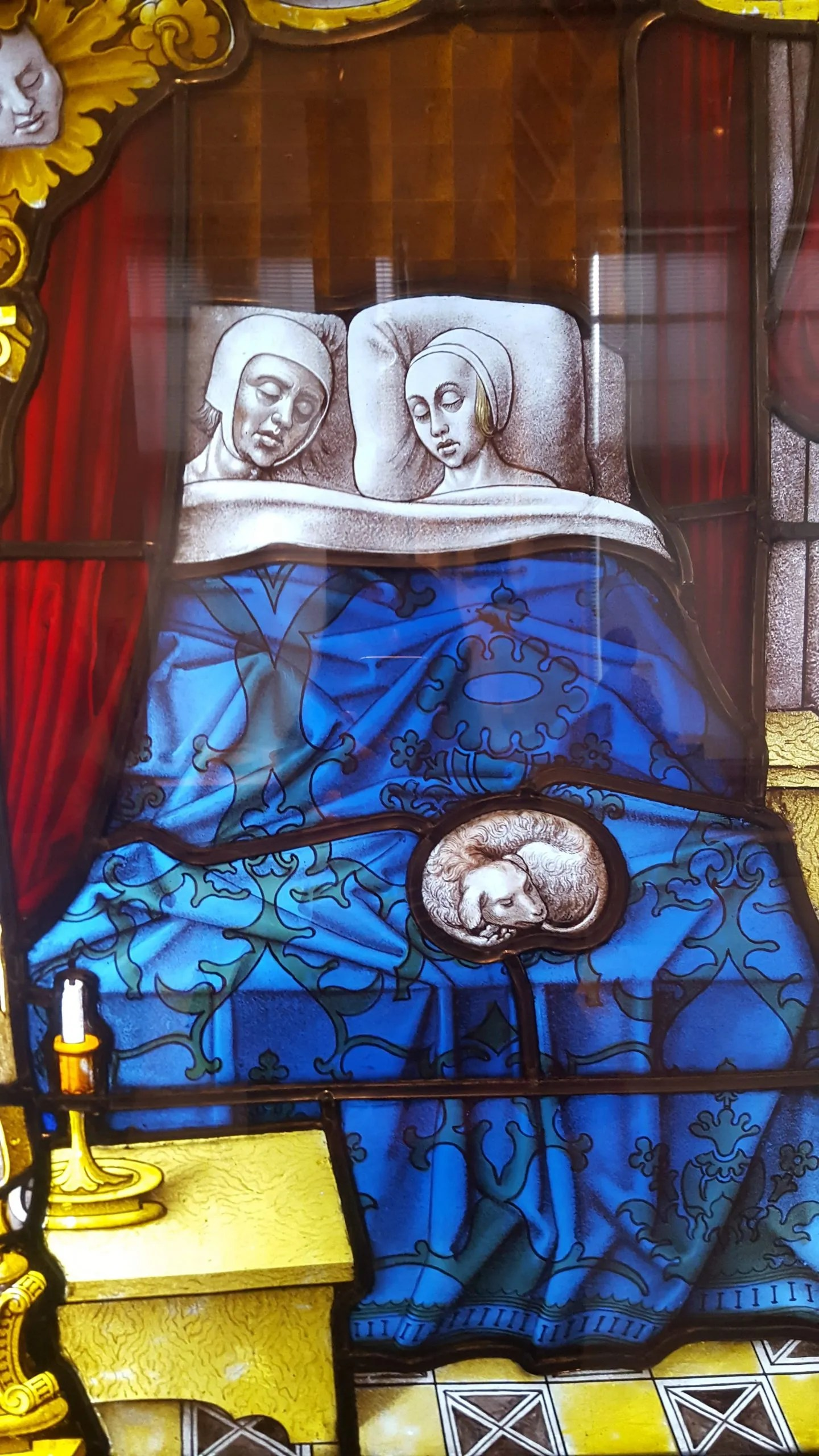 Stained glass showing a sleeping couple with a dog curled up on the bed. Tobias and Sara