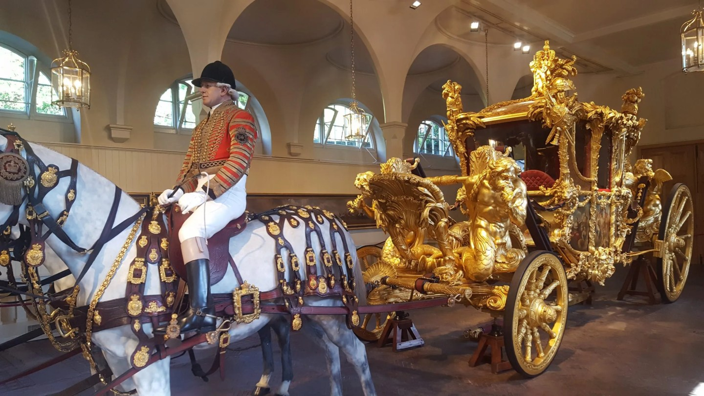Gold State Coach with white horse and rider Royal Mews Buckingham Palace