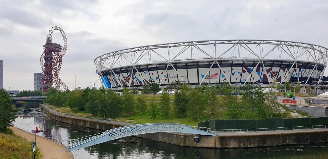 ArcelorMittalOrbit with Olympic Stadium behind River Lea with blue bridge