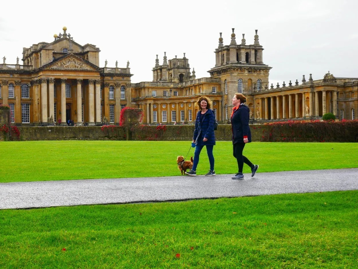 Two women walk a dog in front of Blenheim Palace Oxfordshire