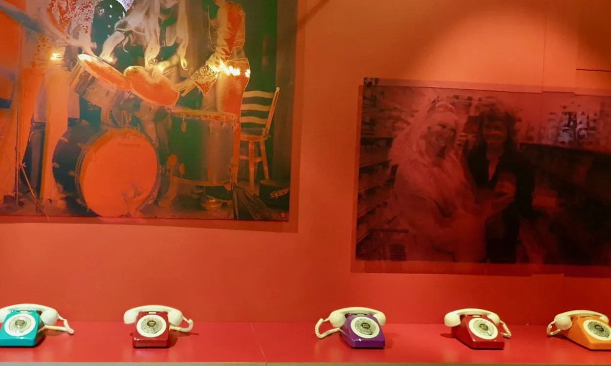 Red walled room with bank of coloured 1970s style phones