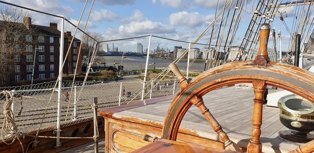 Ships Wheel with views across River Thames to the Shard from deck of Cutty Sark