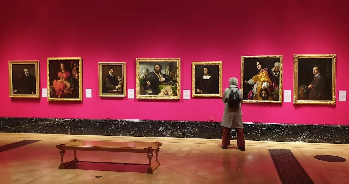 Man looking at paintings masterpieces from Buckingham Palace