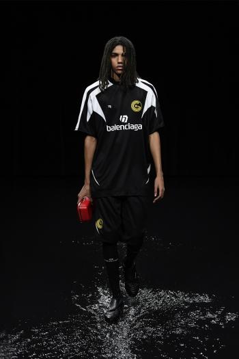 Il rapper Arthur Kopp, con la maglia da calcio e la clutch Lunchbox. Tutto Balenciaga