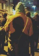 imagen de pessoa de jaqueta amarela vista de costas com a sombra de outra pessoa projetada em suas costas